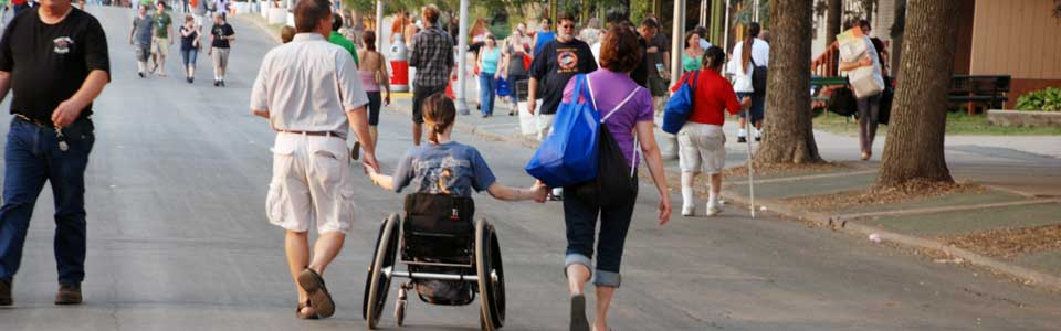 photo of family at the fair, holding hands with middle family member in a wheelchair