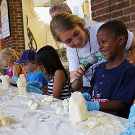 Photo of children carving butter sculptures on the Land O Lakes stage at the Moo Booth