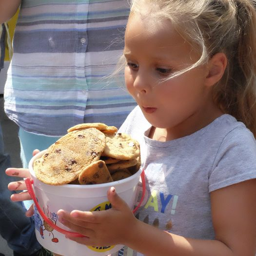 Girl carrying a bucket of chocolate chip cookies